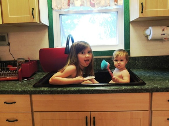 tThe girls in the farmhouse sink.