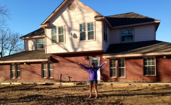 Lauren excitedly standing in front of the house.