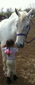 Young (2 year-old) Jordyn having a little talk with Snow before a lead-line class.
