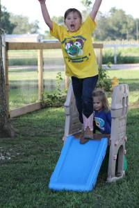 Jordyn showing Kendyll how to jump off the slide.